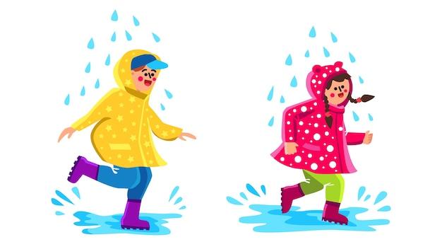 レインコートウォーキング水たまりを着ている子供たち Premiumベクター