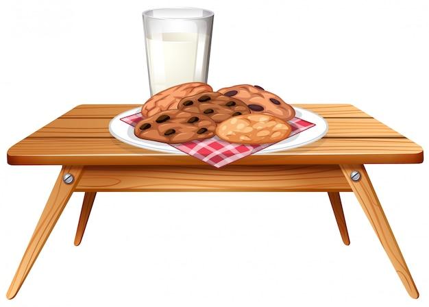 Chocolatechipクッキーとミルクの木製テーブル 無料ベクター