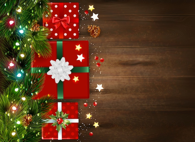 Christmas background with fir tree branches and decorated gift boxes on wooden surface realistic Free Vector