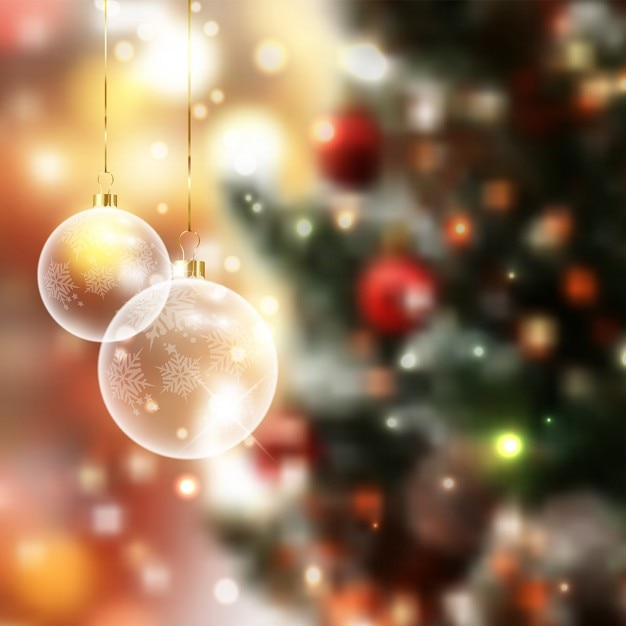 Christmas baubles on a defocussed background Free Vector