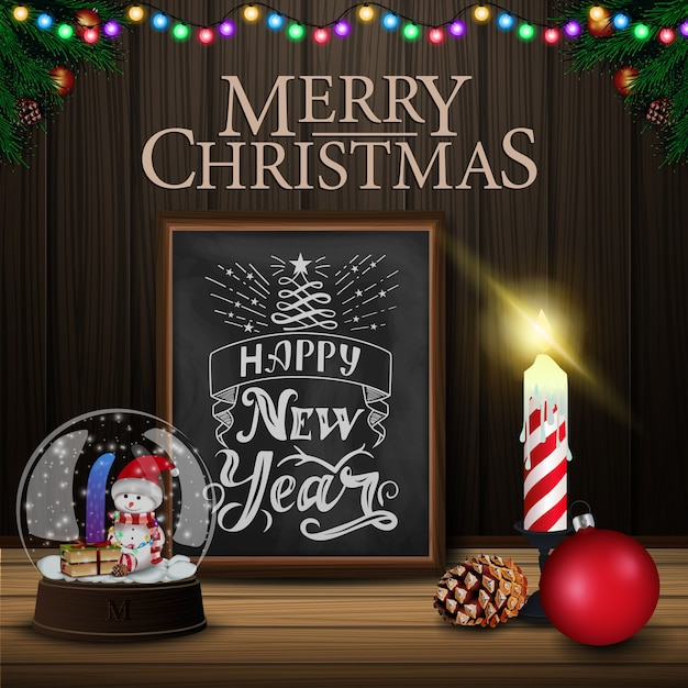 Christmas card with chalkboard, snow globe and candle on wood background Premium Vector