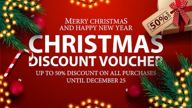 Christmas discount voucher, up to 50% off on all purchases. red discount voucher with presents, christmas tree branches, candy canes and christmas balls Premium Vector