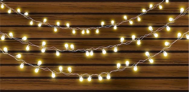 어두운 나무 배경에 고립 된 크리스마스 조명입니다. 광선 갈 랜드 전구 전선. 프리미엄 벡터