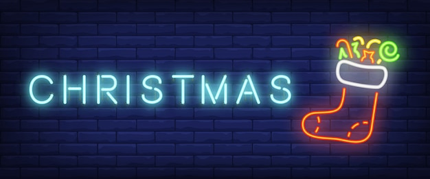 Christmas neon text and felt boot with presents Free Vector