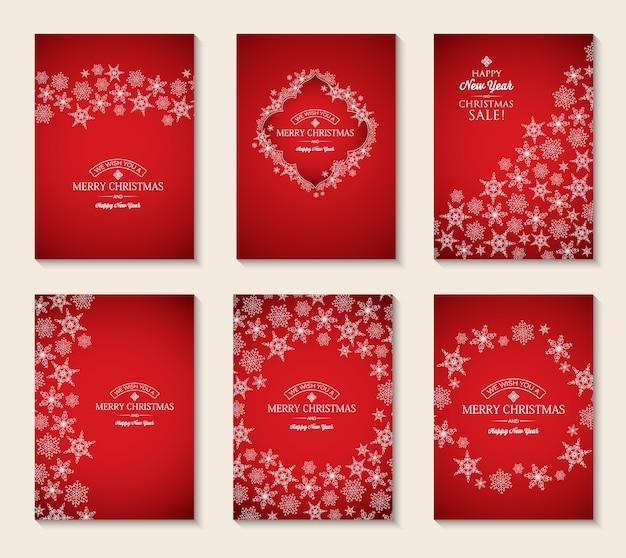 Cartoline di natale e capodanno con iscrizioni di auguri e fiocchi di neve eleganti leggeri su fondo rosso Vettore gratuito