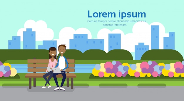 City park african couple man holding laptop woman sitting wooden bench green lawn flowers trees cityscape template background copy space horizontal flat Premium Vector