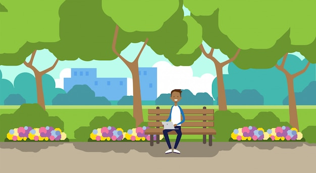 City park african man holding laptop sitting wooden bench green lawn flowers trees cityscape template background horizontal flat Premium Vector