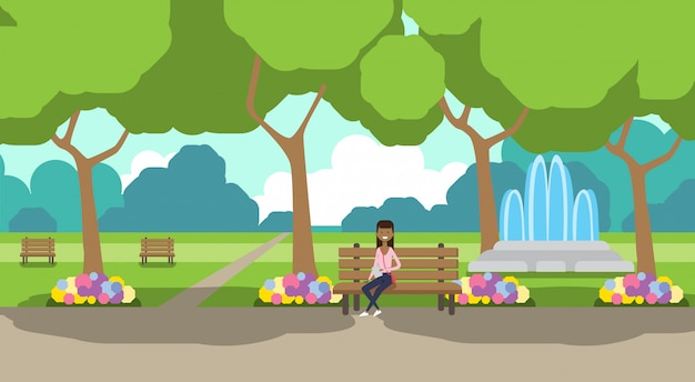 City park african woman holding laptopn sitting wooden bench green lawn flowers fountain trees cityscape template background horizontal flat Premium Vector