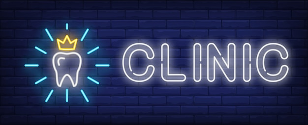 Clinic neon text and shining tooth with crown Free Vector