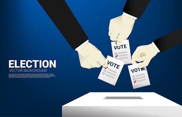 Close up businessman hand put their vote to election box. Premium Vector