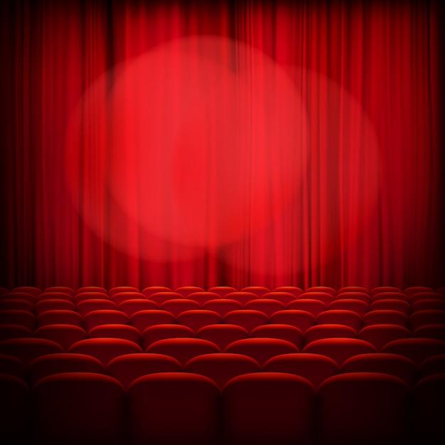スポットライトと座席が付いている閉じた劇場の赤いカーテン。 Premiumベクター