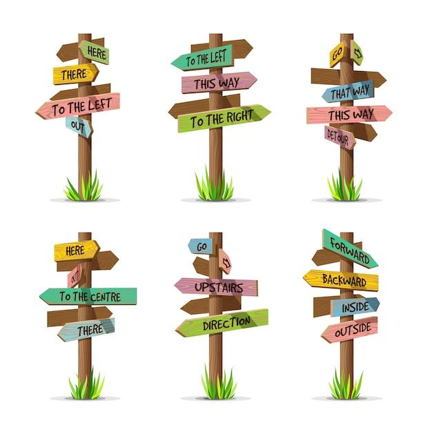 Цветные деревянные стрелки набор направления вывески. деревянная концепция столба знака с травой. доска указателя иллюстрации с текстом, изолированные на белом фоне Premium векторы