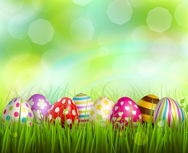 Colorful painted easter eggs on green grass on blurred  with bokeh realistic Free Vector