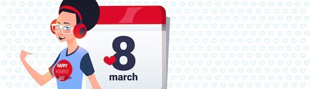 Copyspaceと3月8日日付の背景を持つカレンダーページ上の少女幸せな女性の日ホリデーコンセプト Premiumベクター
