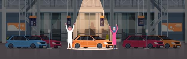 Couple of arab seller presenting new car in dealership center showroom over set of new vehicles horizontal illustration Premium Vector