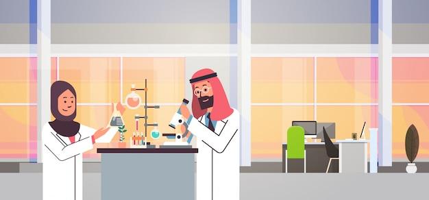 Couple arabian scientists working banner Premium Vector