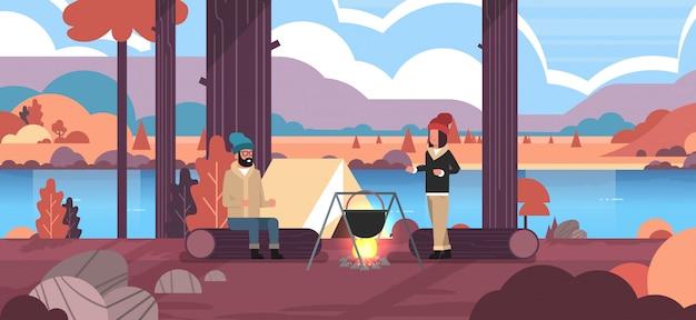 キャンプテントキャンプコンセプト秋の風景自然川山の近くのキャンプファイヤーでボウラー沸騰鍋で食事を調理するログ男性女性の上に座ってカップルハイカー Premiumベクター