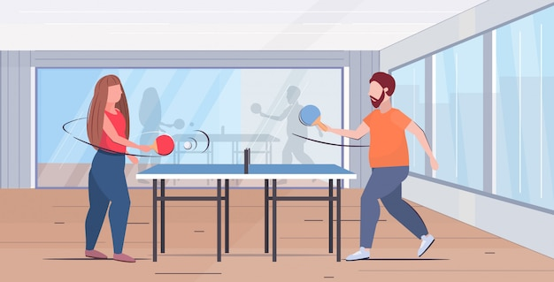 Couple holding rackets overweight man woman playing ping pong table tennis weight loss concept modern gym studio interior flat full length horizontal Premium Vector