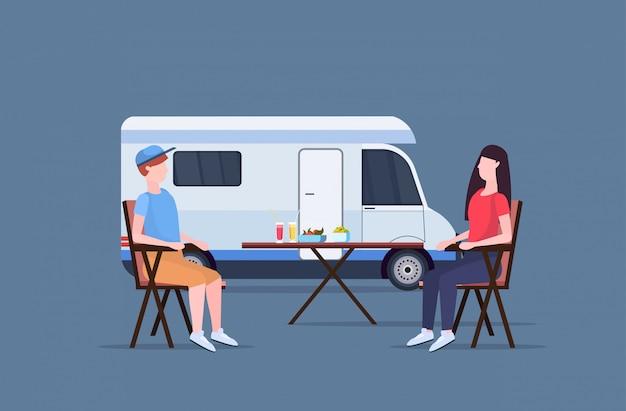 Пара сидя возле стола возле кемпинга семья трейлер грузовик караван автомобиль мужчина женщина тратить время вместе лето концепция плоский полная длина горизонтальный Premium векторы
