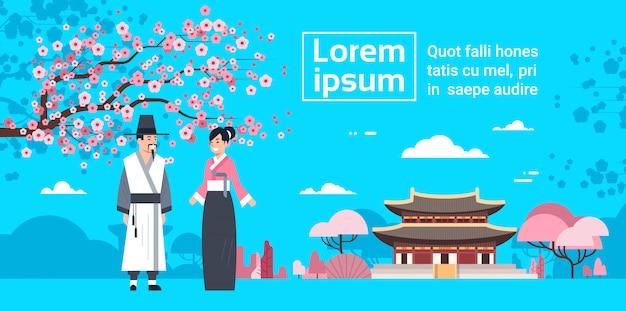 桜の花と韓国宮殿の風景の上のcouplein伝統的な韓国衣装 Premiumベクター