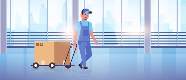 Courier in uniform pushing trolley with cardboard box express delivery service concept worker with hand truck modern office hall interior Premium Vector