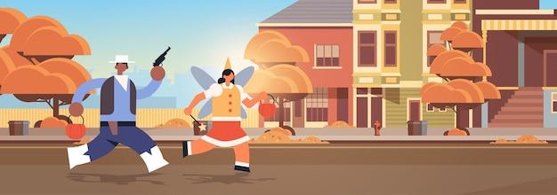 町のトリックでカボチャのバスケットを実行しているカウボーイと妖精のカップルのトリックし、幸せなハロウィーンパーティーのお祝いの概念都市通りの建物外観都市景観 Premiumベクター