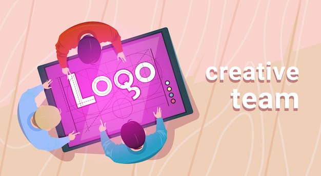 Creative designers team working sit at desk together create web logo on digital tablet in modern office top angle view Premium Vector