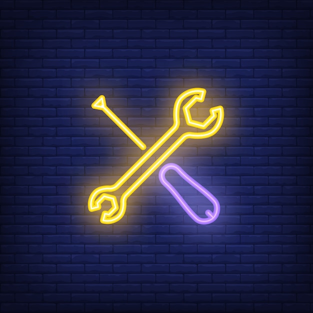 Crossed screwdriver and wrench on brick background. neon style illustration. Free Vector