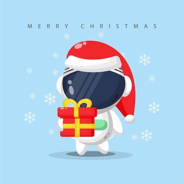 クリスマスの日にギフトボックスを運ぶかわいい宇宙飛行士 Premiumベクター