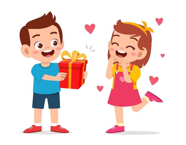 かわいい男の子は誕生日を祝うために小さな女の子にプレゼントを与える Premiumベクター