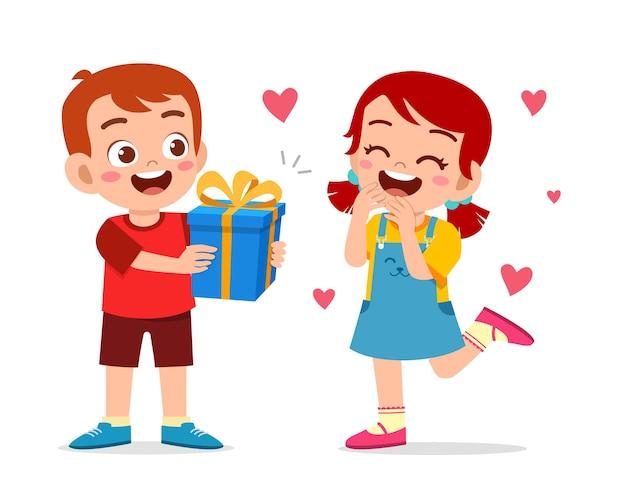 かわいい男の子が小さな女の子にプレゼントを贈ります。 Premiumベクター