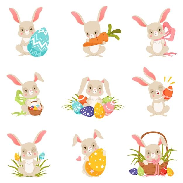 色付きの卵セットを保持しているかわいい漫画のウサギ Premiumベクター