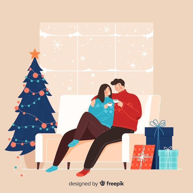 Cute couple enjoying their coffee next to a christmas tree Free Vector