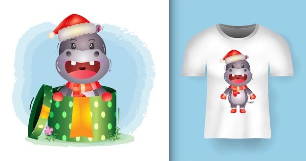 Tシャツデザインのギフトボックスでサンタ帽子とスカーフを使用したかわいいカバのクリスマスキャラクター Premiumベクター
