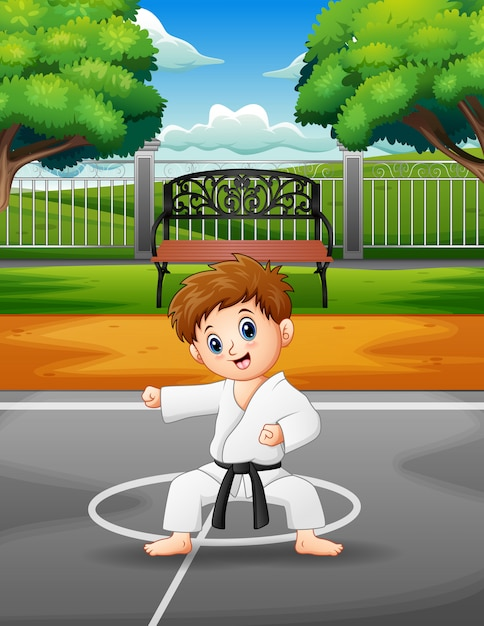Cute little boy practicing karate in the outdoors Premium Vector