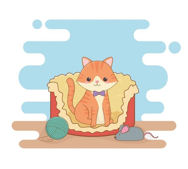 Милый маленький талисман кота в постели с шерстяным рулоном и мышью Premium векторы