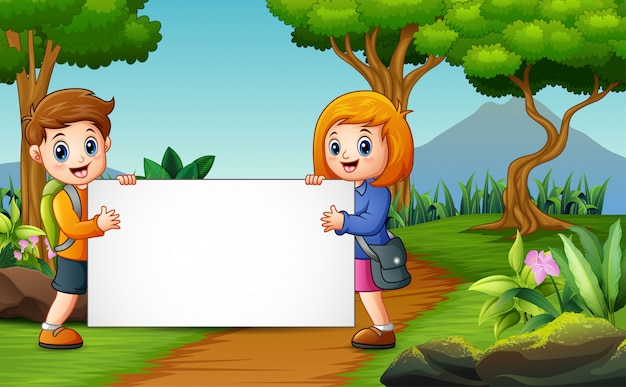 Cute a school children holding whiteboard on the nature Premium Vector