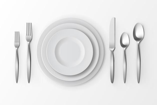 Набор столовых приборов из серебряных вилок, ложек и ножей с тарелками Premium векторы