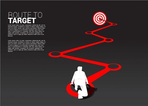 Силуэт бизнесмена готовый для того чтобы побежать на трассе к dartboard. бизнес-концепция пути к цели. Premium векторы