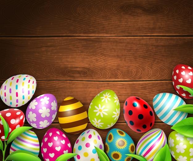 カラフルな卵と緑の葉の画像イラストの木製テーブルテクスチャの上面とイースターの背景 無料ベクター