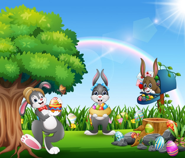 Easter bunnies and colorful egg on the garden Premium Vector