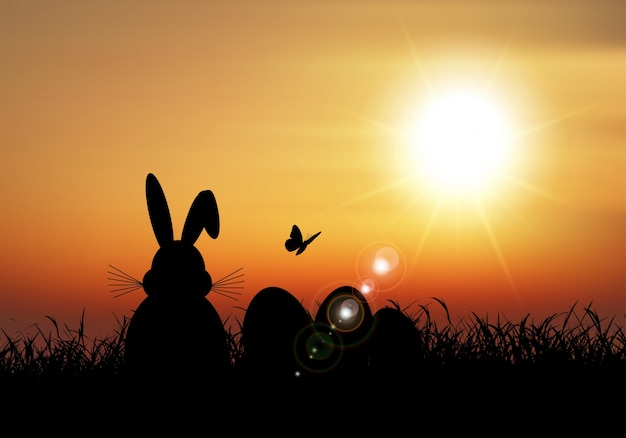 Easter bunny sat in grass against a sunset\ sky