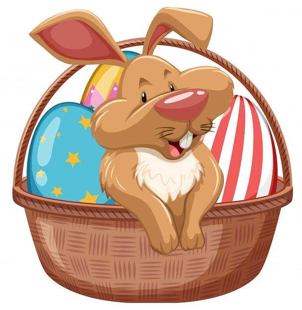 Coniglietto di pasqua con le uova decorate in cestino marrone Vettore gratuito