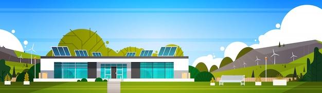 横の風力タービンおよび太陽電池パネルの代替エネルギーの概念が付いているecoの友好的な現代家 Premiumベクター