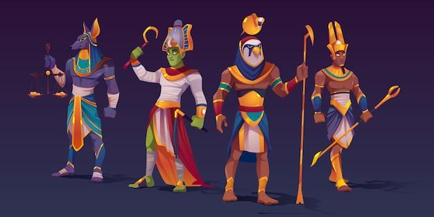 エジプトの神々、アヌビス、ラー、アモン、オシリス。黄金のコインとスタッフ、漫画のベクトル図とスケールとして力の神の属性を保持しているファラオの服で古代エジプトの神の文字 無料ベクター