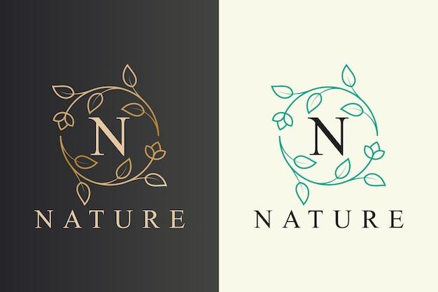 最初の文字でエレガントな花と葉のラインアートスタイルの自然のロゴのデザイン Premiumベクター
