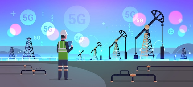 Engineer refinery worker using tablet 5g online wireless system connection oil pump rig energy industrial zone oil drilling fossil fuels production concept horizontal full length Premium Vector