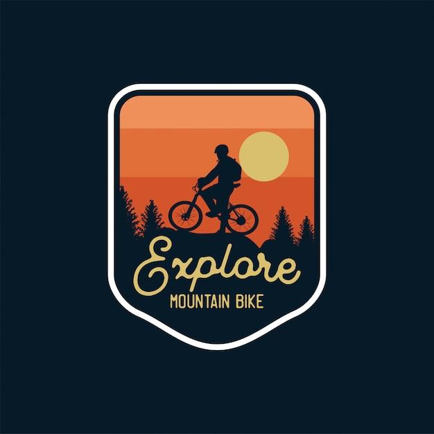 Исследуйте горный велосипед значок силуэт фоне заката. логотип патч Premium векторы