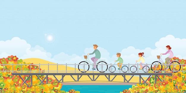 家族は秋に橋の上の自転車に乗っています。 Premiumベクター
