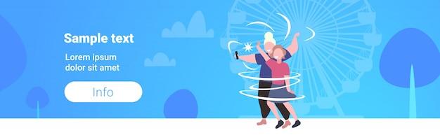 Толстые и худые женщины пара, принимая селфи фото на смартфон камера девушки стояли вместе ожирение путешествия концепция колесо обозрения фон копирование пространство горизонтальный полная длина Premium векторы